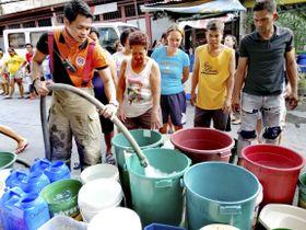 フィリピンの首都マニラで水を配給する消防士=13日(共同)