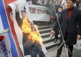22日、北朝鮮視察団が到着したソウル駅の前で、金正恩朝鮮労働党委員長の写真を燃やす保守団体の関係者(共同)