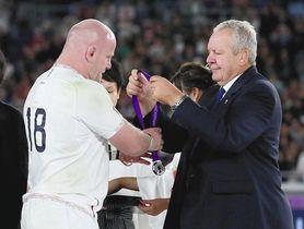 表彰式で準優勝のメダルをかけてもらわず手で受け取るイングランドのコール(左)=2日、日産スタジアムで