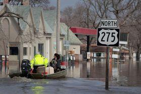 20日、米中西部アイオワ州で冠水した町をボートで移動する人ら(ゲッティ=共同)