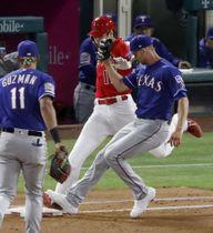 レンジャーズ戦の4回、一塁へのゴロを放ち、一塁へ駆け込むエンゼルス・大谷(中央)。右はベースカバーの投手マイナー。ビデオ判定でセーフとなる=アナハイム(共同)