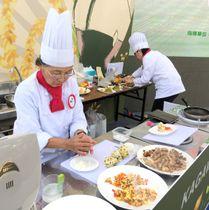 料理対決でおいでまいのおにぎりを作る香川県チームの川染さん(左)=台湾・桃園市