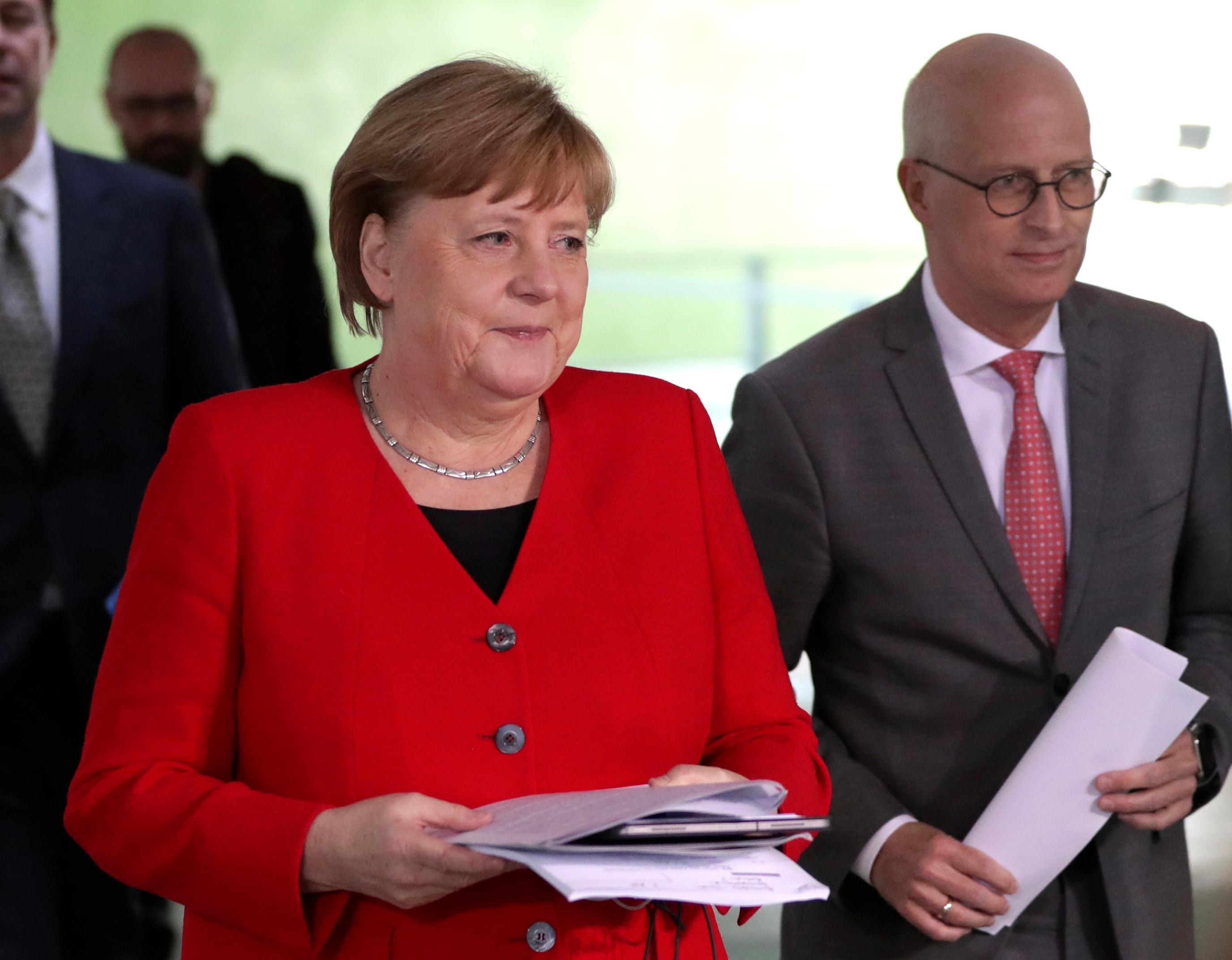 6日、ドイツ・ベルリンで記者会見場に姿を見せたメルケル首相(ロイター=共同)