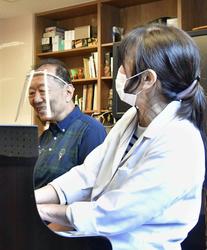 音楽療法を受け笑顔の安達春雄さん。右は飯塚三枝子さん=京都市伏見区の京都医療センター