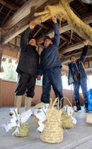 神楽殿で、かんすや大蛇のわら細工などを準備する住民