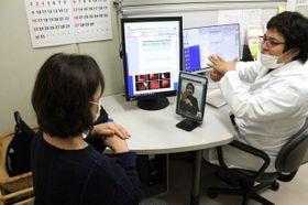タブレット端末に映し出される手話通訳を見ながら、医師(右)から診断結果を聞く女性=岡山済生会外来センター病院