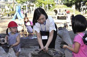 園児と一緒に泥遊びに興じるフォンさん(中)ら