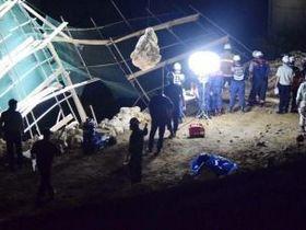 岩石の崩落現場で救助作業を続ける消防隊員ら=15日午後7時40分ごろ、沖縄県北中城村安谷屋