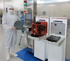 半導体チップの材料となるシリコンウエハーを手に、高性能検査装置について説明するナノシステムソリューションズの赤星治副社長=うるま市
