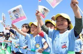 「コナン」の手旗を振って帆船を出迎える子どもたち=長崎市、出島岸壁