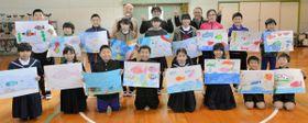 瀬居島初のアートプロジェクトに向けて描いた「海」の絵を掲げる児童ら=坂出市、瀬居小