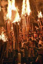京都市の由岐神社一帯で行われた「鞍馬の火祭」で、若者らに担がれる巨大たいまつ=22日夜