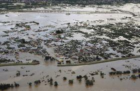 台風19号による大雨で千曲川の堤防(手前)が決壊し、浸水した長野市穂保。奥は北陸新幹線の高架=13日午前9時21分、本社ヘリ「おおづる」から(田中久雄撮影)