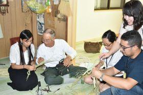 【角谷会長(左から2人目)からしめ縄の作り方を教わる留学生ら=玉城町中角の角谷産業で】