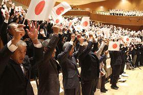 国旗を手に万歳を三唱する参加者=鶴岡市・荘銀タクト鶴岡