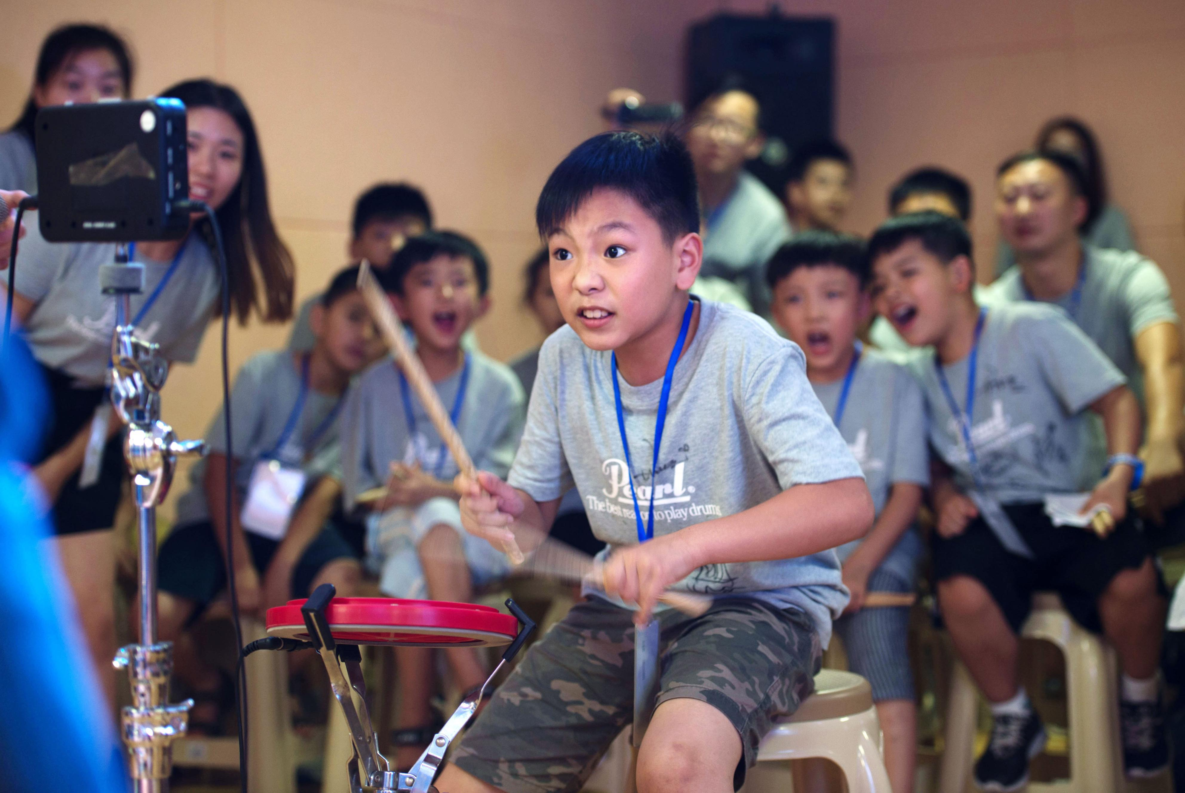 サマースクールでドラム速打ちコンテストに挑戦する男の子=中国山東省臨沂市(撮影・池上まどか、共同)