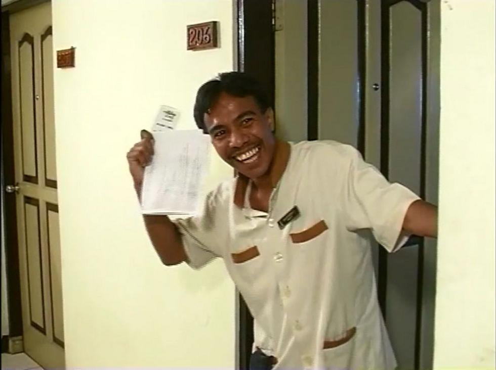 住民投票の有権者登録のために必要な身分証明書を捜し出し、笑顔を見せるマルコス役のセザール(国連制作ビデオより・共同)