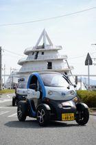 「海のピラミッド」をバックに走る超小型EV=宇城市