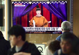 22日、ソウル駅のテレビで報じられる「即位礼正殿の儀」のニュース(共同)