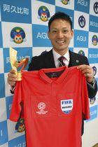 最優秀主審賞のトロフィーと、アジアカップで着用したユニホームを手にする佐藤さん=阿久比町役場で