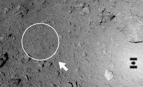 小惑星りゅうぐうへの着陸目標範囲(円)の外側に落ちた目印となるボール(矢印先の白点)。右下は地表に映る「はやぶさ2」の影(JAXA提供)