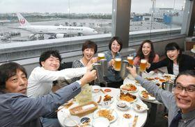 福岡空港のビアガーデンで飛行機を背景に乾杯する客ら=2016年、福岡市