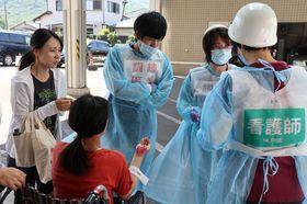 訓練で運ばれて来た負傷者の状況を確認する医師ら=県島原病院