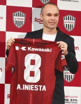 サッカーのJ1神戸に移籍し、記者会見でユニホームを手にポーズをとるスペイン代表MFのアンドレス・イニエスタ=東京都内のホテルで