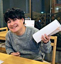 好きな本を手にしながら、満面の笑みを浮かべる澤田健太さん=15日、大阪市旭区