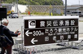 岩手県宮古市田老地区で披露された「震災伝承施設」を示すマークを用いた案内標識。奥は田老防潮堤=20日午前