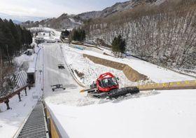 山形市蔵王のジャンプ台で斜面に雪を搬入する重機=11日午後