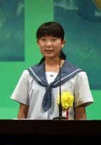 道案内の経験を基に、平和への思いを語る藤田二誓さん=南九州市の知覧文化会館