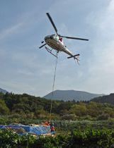 白神岳山頂(後方右奥)へ向けて避難小屋の部材などを運ぶヘリコプター