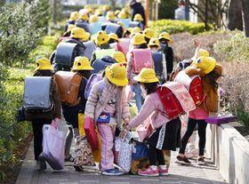 東京都江東区で荷物を手に下校する児童たち。新型コロナウイルス感染拡大防止のため休校となる=28日午後