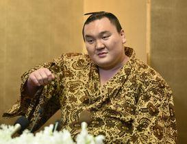 大相撲春場所の優勝から一夜明け、記者会見で痛めた右腕を上げてみせる横綱白鵬関=25日午前、大阪市内のホテル