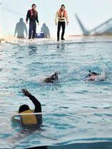 イルカショーのプールで海難救助の様子を実演する「海猿」たち=市立須磨海浜水族園