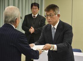 兵庫県明石市役所で当選証書を受け取る泉房穂市長(右)=18日午前