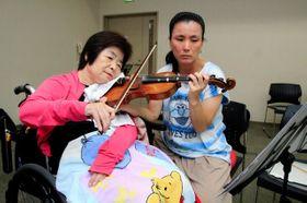 半身まひの母・浩美さん(左)と一緒にバイオリンを弾くたかはたゆきこさん=有馬富士共生センター