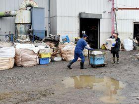 水に漬かり、使えなくなった部品などを運ぶ樹脂加工工場の従業員ら=18日午後、坂戸市紺屋