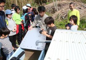 笠井教授(中央)が整備中の雨水浄化・給水システムで、「雨畑」と名付けた集水設備を見学する参加者。右下の波板で雨水が集められる=五島市、赤島