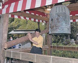 丸太で鐘をたたく参加者=氷見市朝日本町の上日寺