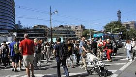 大型商業施設「サクラマチ クマモト」(写真奥)と新市街アーケードを行き交う買い物客=熊本市中央区の市電辛島町電停付近