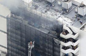 火災があった倉庫で消火活動をする消防隊員ら=12日午後2時38分、東京都大田区(共同通信社ヘリから)