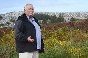 ブドウ畑を占拠されたステファン・スミットさん。右後方の丘に、掘っ立て小屋が密集している=5月3日、南アフリカ・ステレンボッシュ(共同)