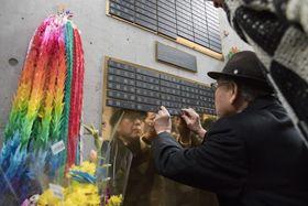 「慰霊と復興のモニュメント」地下の「瞑想空間」の壁に、今村幸司さんの銘板を取り付ける兄の憲司さん=14日午後、神戸市
