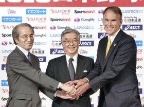 日米野球の記者会見で握手するNPBの斉藤惇コミッショナー(中央)ら=20日、東京都内