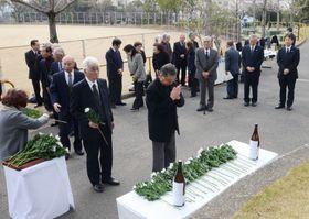 鹿児島県出身の震災犠牲者をしのび、追悼式で献花する参加者ら=神戸市中央区の大倉山公園