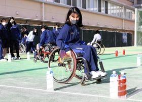 車いすに乗り、陸上スラロームを体験する女子生徒=神戸市兵庫区会下山町3、神港橘高校