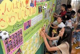 「鮫島先輩頑張って」と応援メッセージを書き込む田原西小の児童たち=20日午前、宇都宮市立伏町