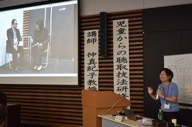 「司法面接」の演習の様子を、ビデオの録画で振り返る仲教授=県警本部